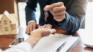 Una persona dando una llave con contrato firmado.