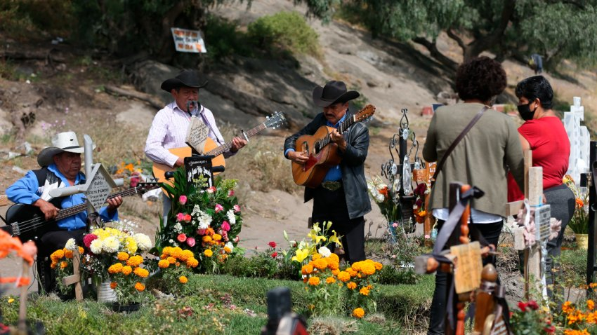 Grupo de músicos interpreta canciones frente a tumbas