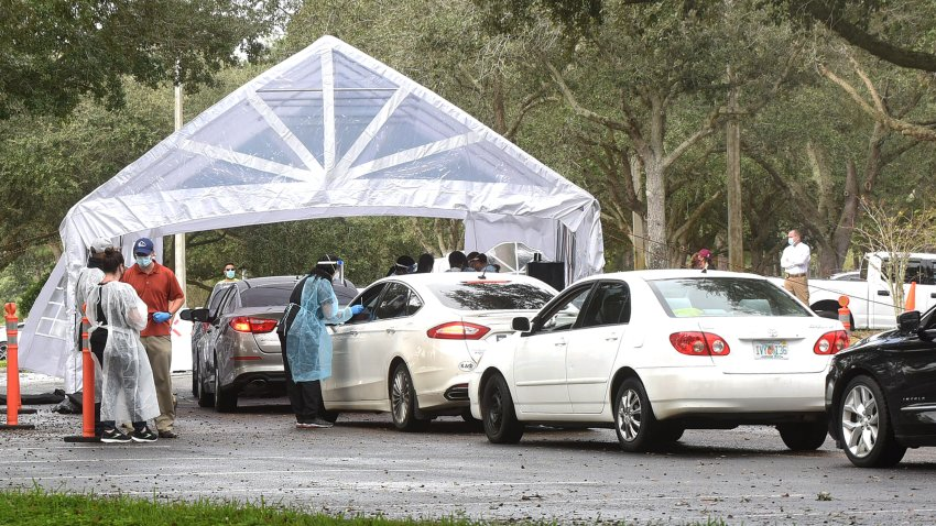 People in cars line up to receive free COVID-19 rapid tests at a drive through site