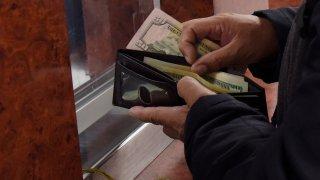 Un hombre saca dólares de su billetera para enviarlos a familiares