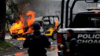 Fotografía de un vehículo incendiado, mientras dos policías ven cómo se quema