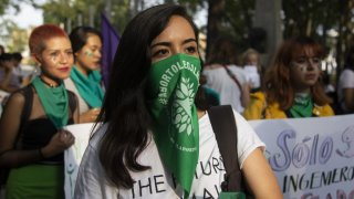 Mujer joven con un pañuelo verde cubriendo parte de la cara en una manifestación a favor del aborto