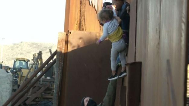Desgarrador: familia migrante salta el muro con niños}